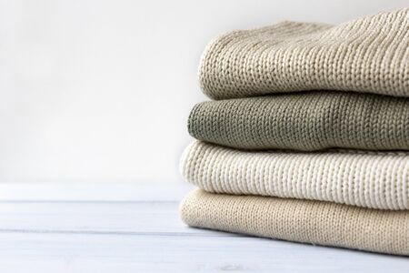 Pile of knitted cashmere sweaters on light blue wooden background. Folded autumn and winter clothing.