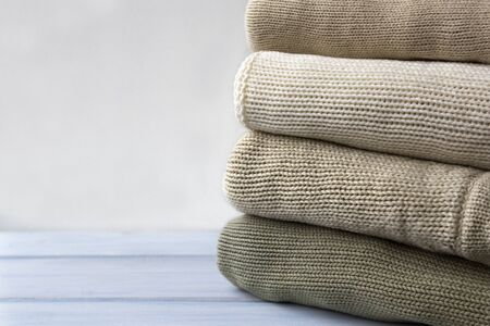 Stack of knitted woolen sweaters on light blue wooden table.  Folded autumn and winter clothing.