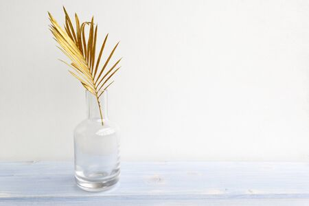Golden palm leaf in glass vase bottle on light blue wooden background. Creative minimal modern concept of organic beauty trend. Stock fotó