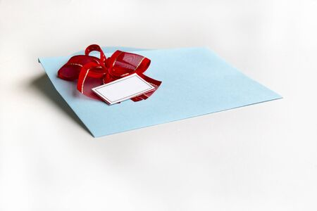Blank paper blue envelope with red ribbon bow, letter for mail on white background, flat lay, top view. Concept postal service or greeting card Stock fotó