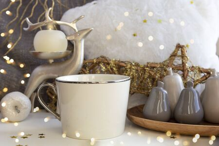 Christmas composition with tea coffee cup, fur pillow, candle, deer and Xmas baubles on New Year background with bright lights and gold stars. Set of warmth and comfort. Stock fotó