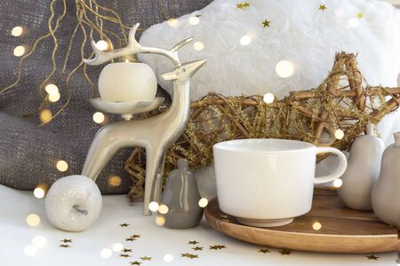 Cup of coffee tea on Christmas composition with candle, deer, fur pillow, and Xmas baubles on New Year background with bright lights and gold stars. Set of warmth and comfort. Stock fotó