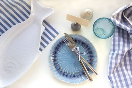 Table setting in marine style - empty plates in shape of fish and blue sea, glass with reflection of water, fork and knife on striped napkins. Flat lay, top view