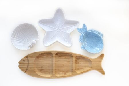 Empty wooden and ceramic plates in shape of fish, starfish and sea shell isolated on white background. Flat lay, top view Stock fotó - 132788929