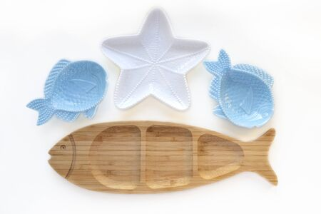 Empty wooden and ceramic plates in shape of fish and starfish isolated on white background. Flat lay, top view Stock fotó
