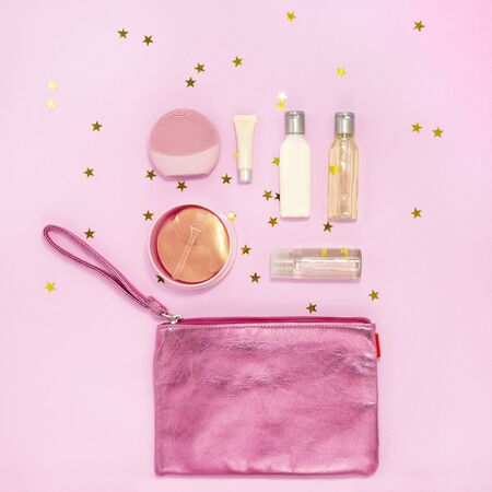 Cosmetic bag with makeup products - cream jars, gel bottles, silicone facial cleansing brush, hydrogel eye patch, on pink background with golden stars. Flat lay, top view Stock fotó - 133050580