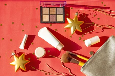 New Year's set of girl makeup cosmetics. Women accessories in silver cosmetic bag -  eyeshadows, face brushes, creams and lotions on red Christmas background with golden stars. Stock fotó - 133053768