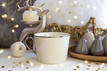 Cup of coffee tea on Christmas composition with candle, deer, fur pillow, and Xmas baubles on New Year background with bright lights and gold stars. Set of warmth and comfort. Stock fotó - 133058019