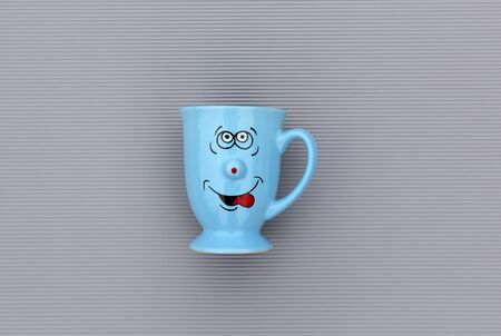 Blue mug of coffee with happy smile face on gray background. Good morning, creative greeting card concept