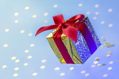 Gold gift box with red ribbon floating on blue background with shining stars and blurry lights. Minimal concept for christmas holidays, birthday, valentine, shopping and sales. Stock fotó
