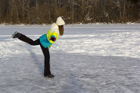 Girl skates on frozen forest lake on sunny frosty day. Makes swallow element. Banco de Imagens