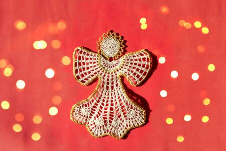 Christmas angel knitted bauble on red New Year background with bright lights, flat lay, top view