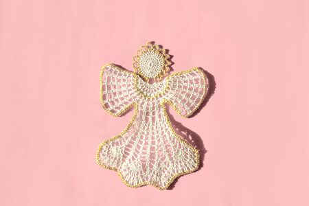 Christmas angel knitted bauble on pink background, flat lay, top view