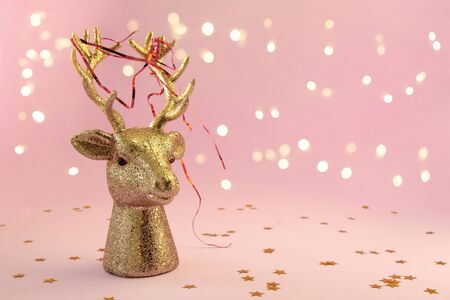 Christmas composition in minimal style - golden deer head on pink background with New Year lights, copy space Stock fotó