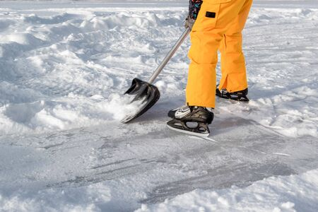 Teenager brush snow with shovel on ice of forest lake for ice skating. Healthy lifestyle.