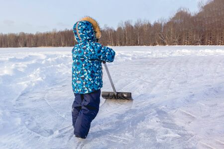 Boy brush snow with shovel on ice of forest lake for ice skating. Healthy lifestyle.