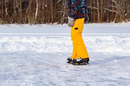 Legs of teenager boy in bright yellow clothe in ice skates, closeup skating shoes in winter, healthy lifestyle.