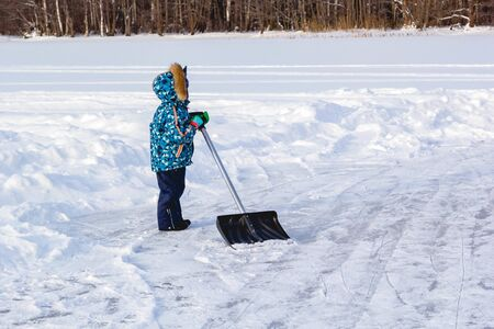 Children brush snow with shovel on ice of forest lake for ice skating. Healthy lifestyle. Banco de Imagens