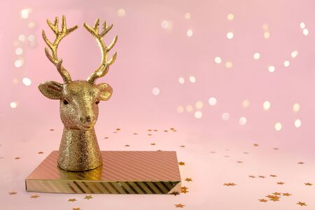 Xmas composition in minimal style - golden deer head on gold, striped box stands on pink background with New Year lights, copy space