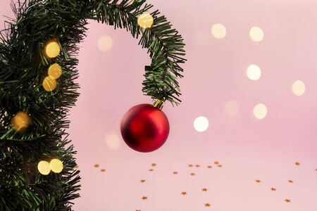 Christmas tree, creative branch with red ball on pink background with New Year lights, copy space