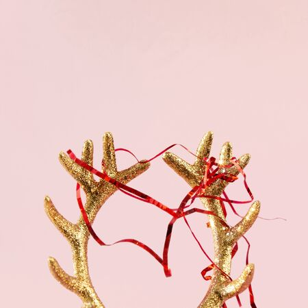 Golden deer horns with red newfoot tinsel on pink background. Xmas composition in minimal style