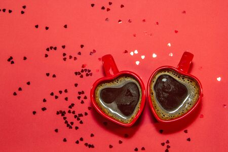 Red pair of mugs of coffee in shape of heart on red background with sparkles hearts. Valentines day concept, symbol of love and romantic. Top view, flat lay, copy space