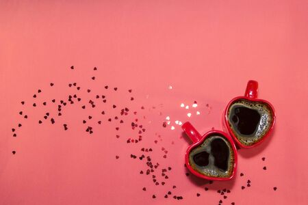 Red pair of cups of coffee in shape of heart on red background with sparkles hearts. Valentines day concept, symbol of love. Top view, copy space Stock fotó