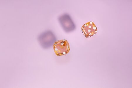 Two glass dice fall, bone to game on pink background. Concept for board games.