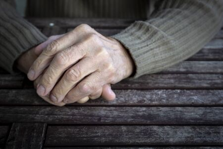 Hands of old senior man with wrinkled palm on wooden table. Copy space, vintage tone