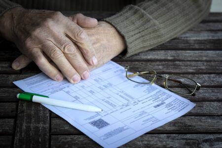 Hands of old senior man fills in utility bills on wooden table. Planning month budget, calculating expen. Wrinkled palm of close up, copy space