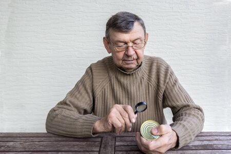 Elderly man reads composition of food product with magnifier. Fine print on can. Hands of old senior with magnifying glass on wooden table, close up, copy space