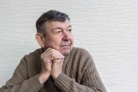 Portrait of elderly man, old senior crossed wrinkled hands. Close-up of face, copy space Stock fotó
