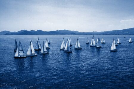 Sailing regatta, group of small water racing boats in Mediterranean, panoramic view with blue mountains on horizon on toning in classic blue color, creative design of 2020