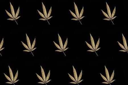 Abstract pattern golden leaves cannabis marijuana on black background in minimal branding creative trend, legalization medical hemp. Minimalist product mockups