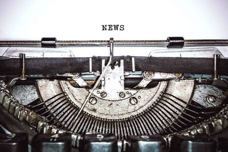 """Old vintage typewriter, retro machine with white sheet of paper and typed text """"news"""", copy space, close up"""