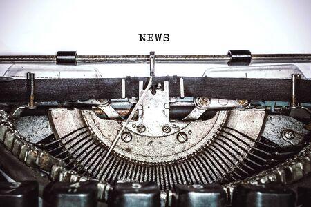 """Vecchia macchina da scrivere vintage, macchina retrò con foglio di carta bianco e testo digitato """"notizie"""", spazio copia, primo piano"""