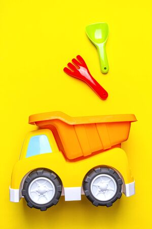 Colorful of plastic children's toys - truck car and shovel, scoop, rake on yellow background, copy space, close-up, vertically