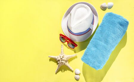 Set travel accessories on yellow background. Beach hat, sunglasses, towel, starfish, shells for woman's summer holidays. Banner fashion concept, top view, flat lay Stockfoto