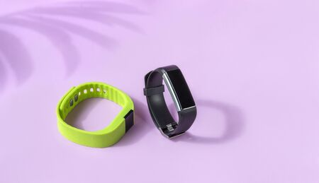 Activity smart trackers on light pink background. Black and green fitness health watch, sport bracelets