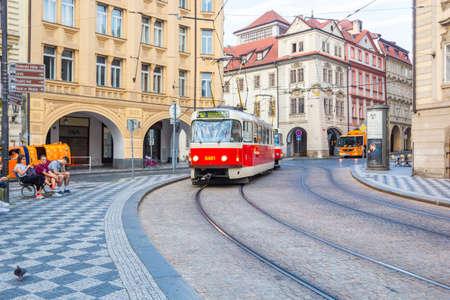 PRAGUE, CZECH REPUBLIC - AUGUST 26, 2019: Old trams on main square of Prague's Mala Strana next to St. Nicholas Church, Prague, Czech Republic