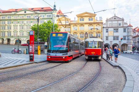 PRAGUE, CZECH REPUBLIC - AUGUST 26, 2019: Old and modern trams on main square of Prague's Mala Strana next to St. Nicholas Church, Prague, Czech Republic