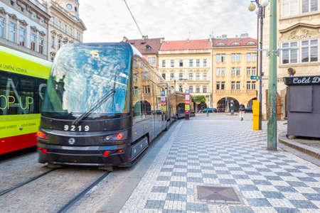 PRAGUE, CZECH REPUBLIC - AUGUST 26, 2019: Modern trams on main square of Prague's Mala Strana next to St. Nicholas Church, Prague, Czech Republic