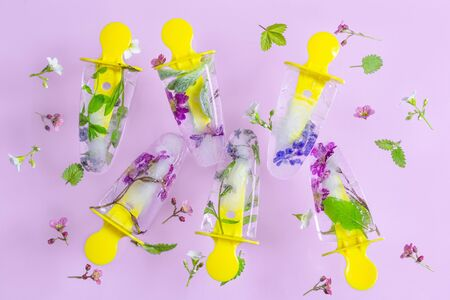 Flying ice pop, ice cream with flowers on pink pastel table. Fresh bright frozen ice on summer background.