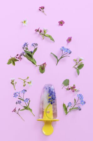 Flying ice pop, ice cream with flowers on pink pastel table, vertical. Fresh bright frozen ice on summer background.