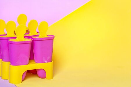 Homemade , ice cream sticks on bright pink yellow colors background