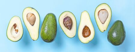 Banner fresh avocado halves with seed flying on blue background. Minimal concept organic summer food. Flat lay, top view, copy space