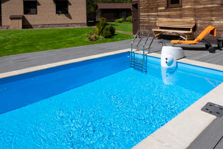 Swimming pool with clear water, deck chair in backyard of country house