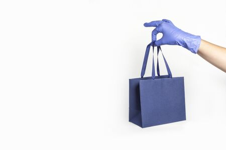 Woman hand in glove with gift paper bag on white background. Delivery of food, groceries, home shopping. Protection for COVID-19 Coronavirus precautions. Stok Fotoğraf