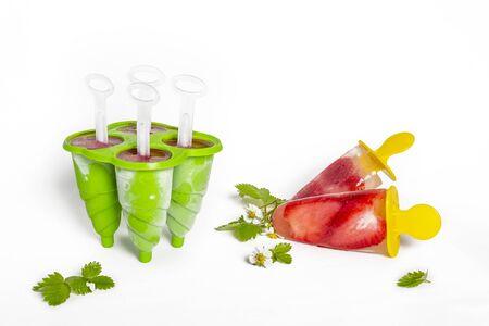 Homemade strawberry  frozen juice, ice cream sticks on white background. Bright refreshing taste of summer
