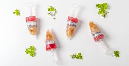 Frozen fruit juice on stick, ice cream and fresh green leaves on white